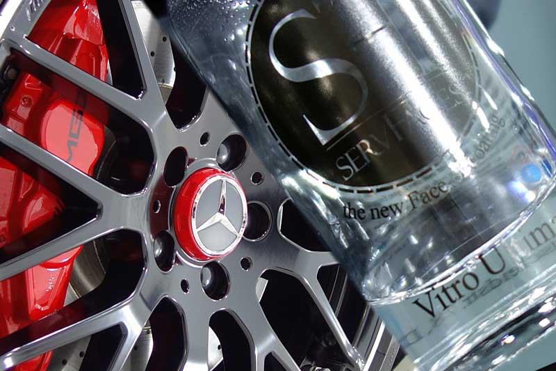 Das Foto zeigt eine Felge mit Keramikversiegelung eines Mercedes AMG Modells. In der anderen Hälfte des Bildes ist ein Foto einer Keramikversiegelung für Scheiben.
