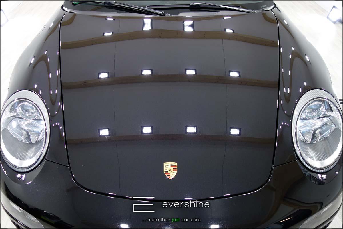 Das Foto zeigt die Motorhaube eines Porsche 911 nach der Fahrzeugaufbereitung - Lackkorrektur. Die Farbe des Fahrzeugs ist schwarz. Es ist deutlich zu erkennen dass der Lack wieder frei von Defekten ist.