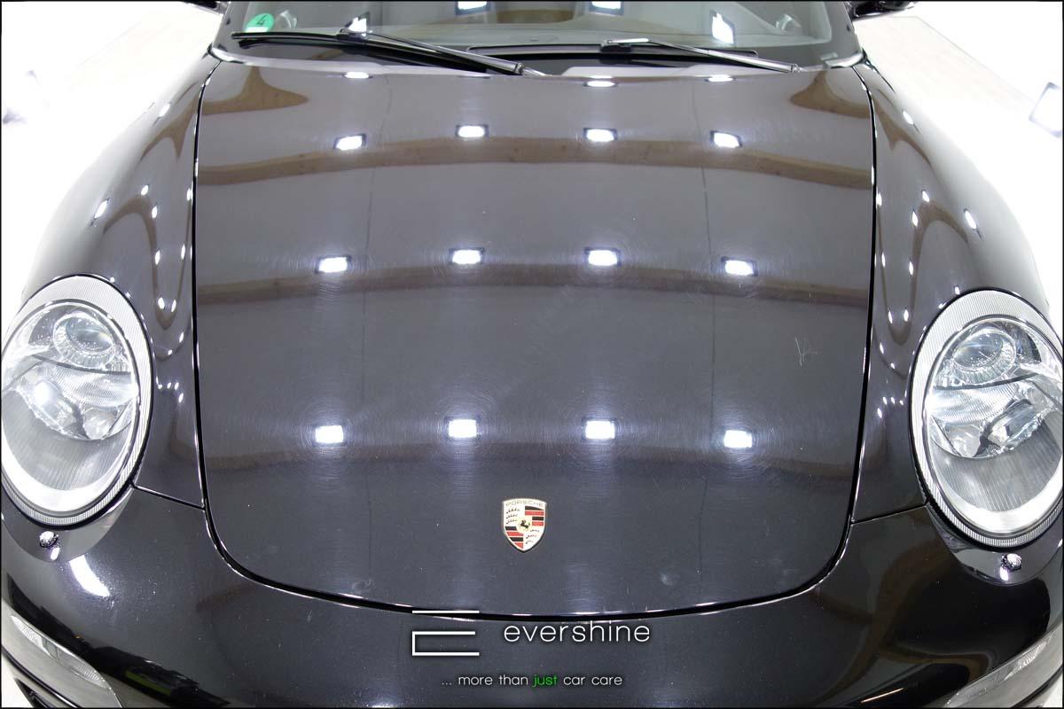 Das Foto zeigt einen Porsche 911 vor der Fahrzeugaufbereitung und Lackkorrektur. Man erkennt deutlich Waschkratzer, Hologramme und andere Lackdefekte. Das Fahrzeug ist schwarz und steht in einem gut ausgeleuchtetem Raum